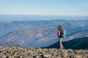 Young athletic woman backpacker standing on the ridge of the mountain enjoying the open view on the big mountains. Rear view, sunny autumn day.