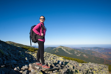 Young female backpacker standing on rocky mountain peak smiling and looking to the camera. Fall.