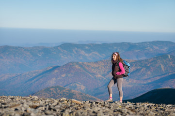Young athletic girl backpacker walking on the ridge of the mountain enjoying the open view on the big mountains. Rear view, sunny fall day.