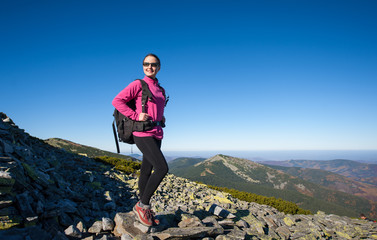 Young female backpacker standing on rocky mountain peak smiling and looking at beautiful mountain nature landscape. Fall.