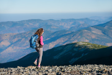 Young woman tourist is walking on mountain plato with big backpack on. Beautiful mountains on background. Sunny autumn day.
