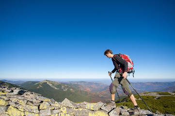 Young man backpacker walking on the rocky ridge of the mountain with beautiful high altitude landscape view on the background. Hiker using trekking sticks. Fall.