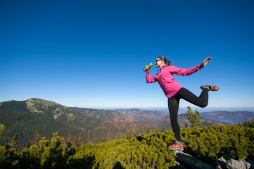 Happy lady hiker celebrating reaching her goal at mountain peak rock. Woman is wearing pink jacket and sunglasses, standing on one leg and holding thermos.