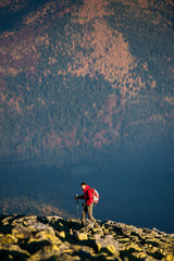 Young man hiker walking on the rocky mountain against beautiful mountain on background, autumn colors. Side view. Ecotourism and healthy lifestyle concept. Copy space. Sunny fall day.