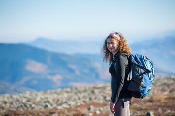 Portrait of young girl enjoying nature on backpacking trip in the mountains. Girl smiling and looking into the camera.