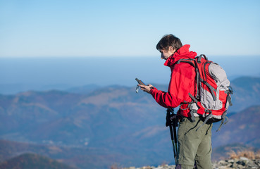 Portrait of young man backpacker standing on the peak of the mountain and looking at gps coordinates. Beautiful mountains on the background. Tourist wearing red jacket and red backpack.