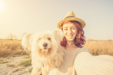Attractive caucasian girl is doing selfie with her dog in the countryside - caucasian people - people, animal, technology and lifestyle concept