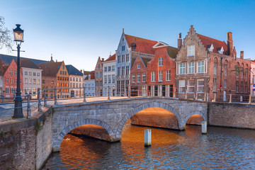 Foto op Canvas Brugge Scenic city view of Bruges canal with beautiful medieval colored houses and sunny bridge in the morning, golden hour, Belgium