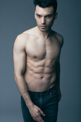 Muscular young sexy guy posing in studio in jeans and naked torso