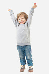 Kid raised his hands to the top. Full length. Gray no image sweater and blue jeans. Mockups template
