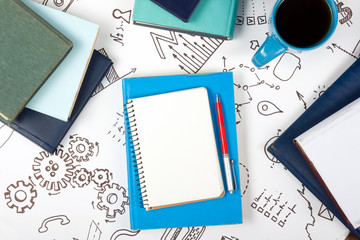 Office table desk with blue supplies, white blank note pad, cup, pen, pc, crumpled paper, flower on wooden background. Top view