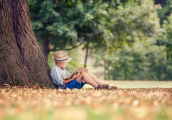 Reading boy sitting under big tree in park