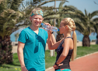 Two sporty people drink a water after outdoor training