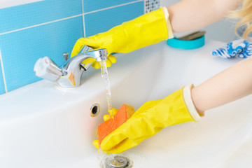 Cleaning - cleaning bathroom sink and faucet with detergent in gloves