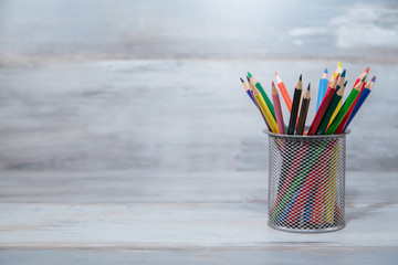 Color pencils in the stand holder on the wooden table vintage background