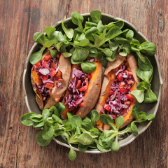 baked sweet potatoes in the oven with carrots and cabbage