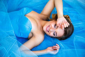 Beautiful bride lying on gorgeous blue dress Cinderella style in a morning