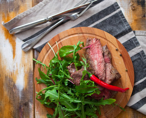 Tasty cut meat steak with greens and arugula on a wooden plate a