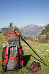 Camping with backpack in the mountains on a sunny summer day.