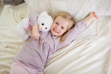 Child girl in the bed with teddy bear