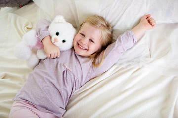 Child girl in the bed with white teddy bear