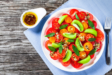 tomato salad with kiwifruit, dressing olive oil with aromatic he