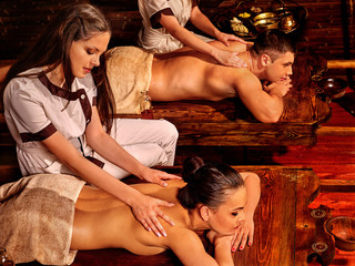 Loving couple  having oil Ayurveda spa treatment massage on wooden bed. Massage for couples in love.