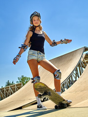 Portrait of teen girl  standing on his skateboard aganist blue sky outdoor. Skate sport.