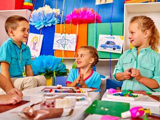 Group kids mold from plasticine  in kindergarten. Modeling School.