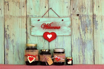 Welcome sign with red heart hanging over jars of fruit jelly
