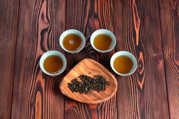 Mug of green tea on wooden background. Imitation Cat's footprints.