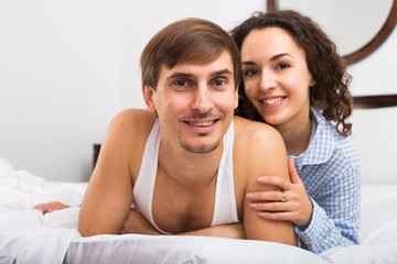 Portrait of happy couple awake in bed