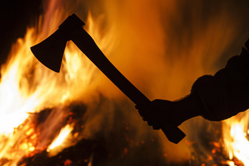 hand with an ax on a background of a burning forest