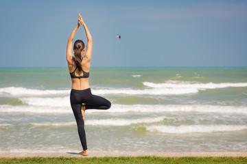 Молодая женщина занимается йогой на берегу моря. Поза дерева.