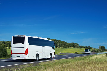 White buses driving on asphalt road in a rural landscape. Sunny summer day with blue skies.