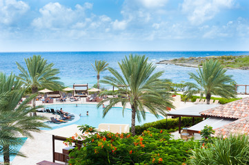 island resort with chaise lounges and cabanas around a pool with a beach and blue skies and palm trees