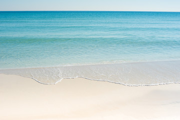white sand beach with blue water and blue sky