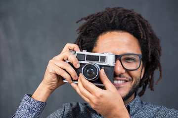 Happy hipster man smiling with toy camera on rustic backgorund