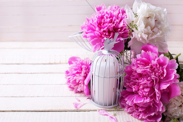 Fresh pink peonies flowers and candle on white painted wooden ba