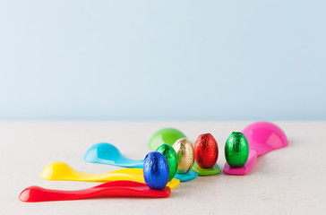 Chocolate Easter eggs wrapped in colorful foil placed on measuring cups. Shallow depth of field