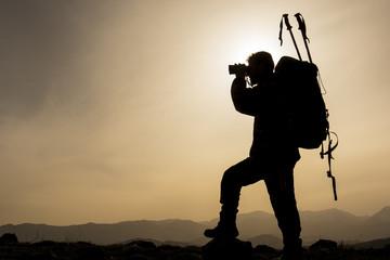 dürbünle dağlarda gözlem yapan dağcı