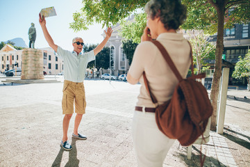 Woman taking photos of an excited senior man