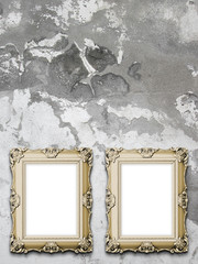 Close-up of two brown Baroque picture frames on weathered concrete wall background