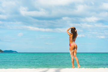 Beach vacation. Hot beautiful woman in bikini standing and  enjoying looking view of beach ocean on hot summer day.