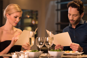 Couple reading menu at restaurant