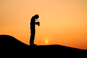 Silhouette picture of a man prepare to take photograph in sunset
