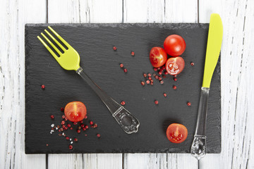 Red fresh tomatoes on chopping board with knife