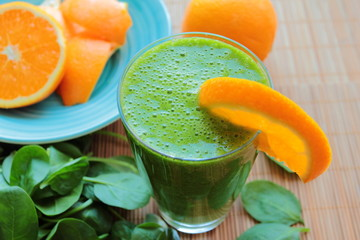 Healthy smoothie with spinach and orange in a glass