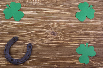 Fabric green clover leaves with horseshoe on wooden background.