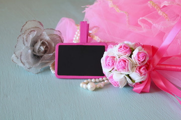Small girls party outfit: crown and wand flowers next to small empty chalkboard on wooden table. bridesmaid or fairy costume